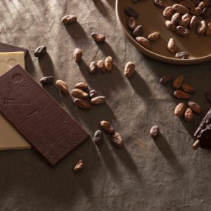 Organic chocolate bars next to cacao beans and a cacao pod