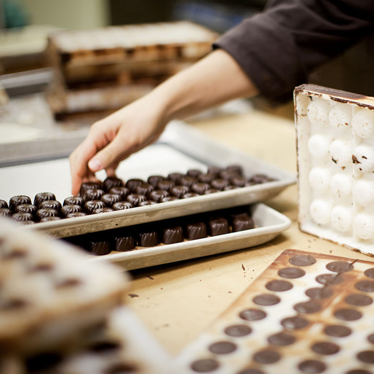 Hands emptying chocolates into a tray from the mould cavities